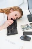 打呵欠在键盘的睡着的女实业家在办公室 图库摄影