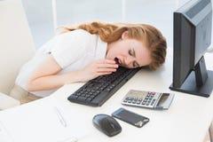 打呵欠在键盘的睡着的女实业家在办公室 库存照片