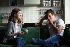 打呵欠年轻的丈夫得到乏味听激动的妻子ta 免版税图库摄影