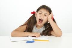 打呵欠疲乏的孩子,当做她的家庭作业时的她 免版税库存图片