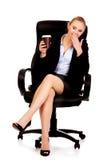 打呵欠的女商人坐轮椅和拿着咖啡 免版税库存照片