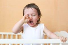 打呵欠的婴孩在白色床上 免版税库存照片