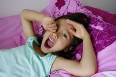 打呵欠年轻亚裔的女孩。 库存照片