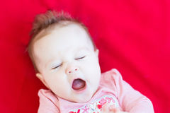 打呵欠滑稽的卷曲的女婴 免版税库存照片