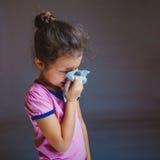 打喷嚏的十几岁的女孩遭受流鼻水 库存照片