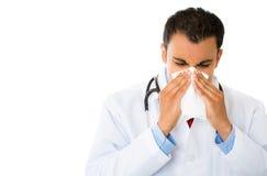 打喷嚏的病的男性医生 图库摄影