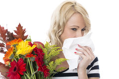 打喷嚏从花粉症过敏的少妇拿着一束花和组织 免版税库存照片