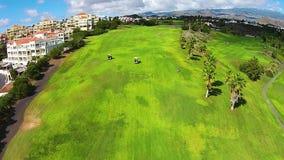 打在一个巨大的高尔夫球场的一个人高尔夫球,在草,空中射击的两辆高尔夫车 股票视频
