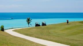 打在一个热带高尔夫球场的高尔夫球,在看海洋 库存图片