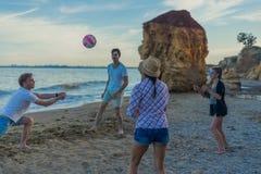 打在一个狂放的海滩的朋友排球在日落期间 免版税库存图片