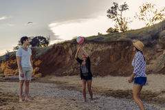 打在一个狂放的海滩的朋友排球在日落期间 库存照片