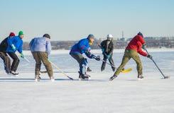 打在一条冻河德聂伯级的小组另外年龄人民曲棍球在乌克兰 免版税库存图片