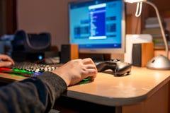 打在个人计算机的年轻十几岁的男孩电子游戏 免版税库存照片