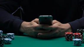 打在他的智能手机的人扑克,陷入赌博娱乐场大气,应用 股票录像