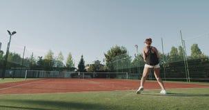 打在充分的网球场的年轻女性网球比赛 射击在红色史诗 4K 股票视频