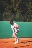 打在公开法庭的年轻人网球 免版税库存照片