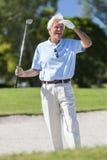 打在地堡的愉快的老人高尔夫球 免版税库存照片