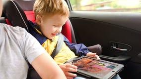 打在垫的愉快的男孩比赛在汽车旅行期间 影视素材