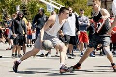 打在城市squa的一个小组年轻人街道篮球 免版税库存图片