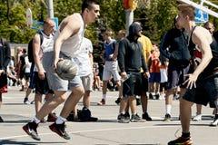 打在城市squa的一个小组年轻人街道篮球 免版税库存照片