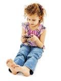 打在她的移动电话的小女孩比赛 免版税库存照片