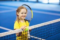 打在室内法院的孩子网球 免版税库存照片