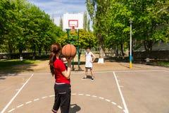 打在室外法院的夫妇篮球 免版税库存照片