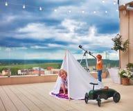 打在屋顶露台的逗人喜爱的愉快的孩子比赛 免版税库存照片