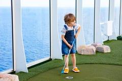 打在巡航划线员的小孩男孩微型高尔夫球 免版税图库摄影