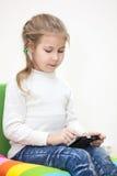 打在手机的孩子比赛,坐室内 免版税库存照片