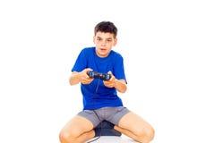 打在控制杆的男孩电脑游戏 免版税图库摄影