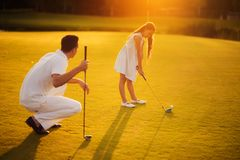 打在日落背景的女孩高尔夫球 人在她旁边在高尔夫俱乐部蹲并且倾斜 免版税库存照片