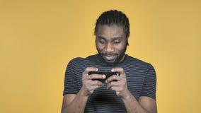 打在智能手机的偶然非洲人比赛隔绝在黄色背景 股票视频