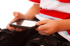 打在智能手机的小男孩比赛 免版税图库摄影