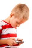 打在智能手机的小男孩比赛 库存照片
