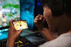 打在智能手机的少年游戏玩家男孩的图象电子游戏和 库存照片