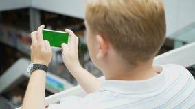 打在智能手机的年轻少年比赛在咖啡馆 打在智能手机的年轻愉快的人比赛 智能手机打开  股票视频
