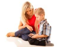 打在智能手机的母亲和儿子电子游戏 库存图片