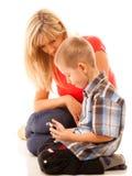 打在智能手机的母亲和儿子电子游戏 免版税库存图片