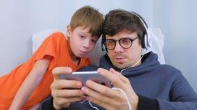 打在智能手机的玻璃和耳机的人一场比赛有他的儿子的 游戏玩家放松 影视素材