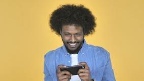 打在智能手机的美国黑人的人比赛在黄色背景 股票录像