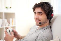 打在沙发的年轻可爱的人电子游戏 免版税库存照片