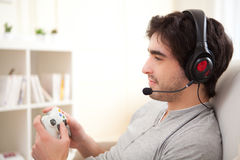 打在沙发的年轻可爱的人电子游戏 免版税库存图片