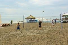 打在沙子的青年人沙滩排球在黑海 库存照片