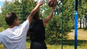 打在法院户外的两位运动员篮球,滴下和丢失通过篮子的一位运动员 股票录像