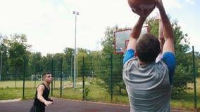 打在法院户外的篮球有朋友的,滴下和错过篮子的年轻运动员 影视素材