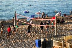 打在海滩的人们排球 免版税图库摄影
