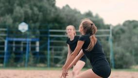 打在海滩的年轻女人排球在进行攻击的队击中球 慢动作命中的女孩 股票录像