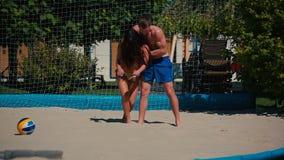 打在海滩和女孩的年轻夫妇排球在沙子倒下 股票录像