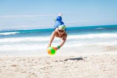 打在海滩的可爱的年轻人排球 库存照片